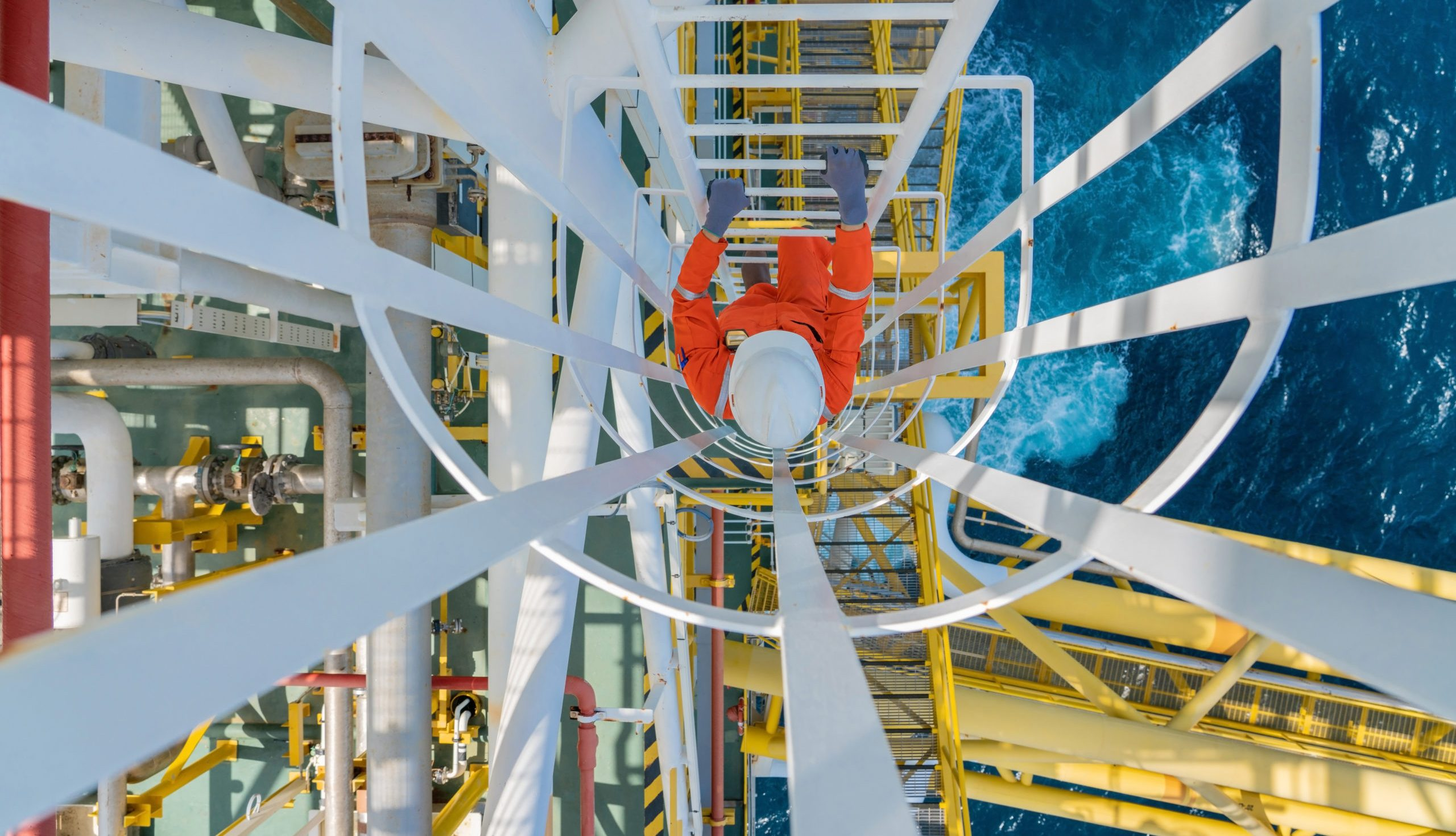 Offshore oil and gas production operator climb up to gas processing platform to checking condition of gases condensate treatment and utility process.
